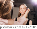 makeup artist brushing eyebrows of a client 49152185