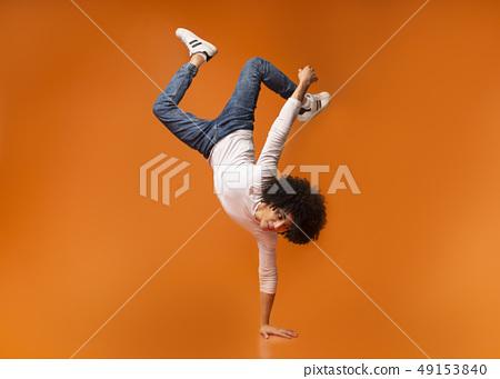 Black man balancing on one hand on orange 49153840