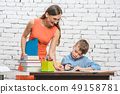 Teacher helping student with difficult task in school  49158781