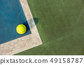 Fluorescent yellow tennis ball in the corner on blue acrylic surface 49158787