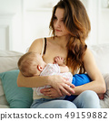 young mother breastfeeding her little son 49159882