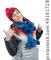 Beautiful young woman in winter clothes is showing 49161728
