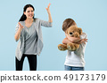 Angry mother scolding her son in living room at home 49173179