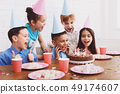 Boy blowing candles on birthday cake, celebrating with friends 49174607