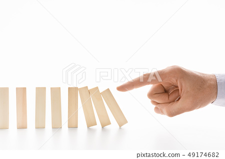 Male hand pushing dominoes on white background 49174682