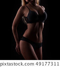 woman in black pants on dark background 49177311