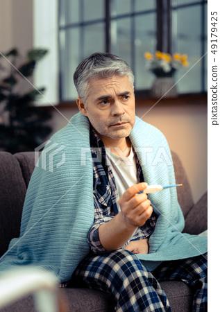 Sad cheerless man thinking about his illness 49179425