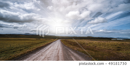Empty dirt road through countryside landscape. 49181730
