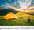 Tourist camp in mountains with tent and cauldron over fire at sunset 49188959