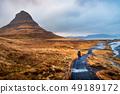 Traveler at famous Kirkjufellsfoss waterfall in 49189172
