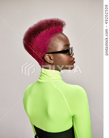 Close-up indoor portrait of lovely girl with colorful hair. Studio shot of graceful young woman with 49202509