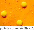 Three yellow spheres on orange background. Close 49202515