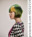 Close-up indoor portrait of lovely girl with colorful hair. Studio shot of graceful young woman with 49202559