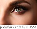 Female left emerald green coloured eye extreme closeup 49203554