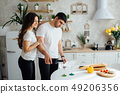 Smiling lovers drinking white wine in the kitchen 49206356