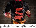 Closeup of chef throwing raw beef steaks 49208459