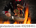 Closeup of chef throwing hamburger steaks 49208461