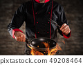 Closeup of chef holding frying pan above grill. 49208464