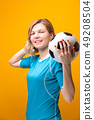 Photo of blonde with soccer ball on yellow background 49208504