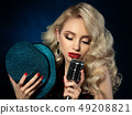 Portrait of pretty blond female singer holding microphone 49208821