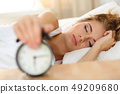 Sleepy young woman trying kill alarm clock 49209680