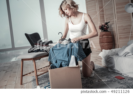 Slim young woman packing clothes of ex boyfriend into boxes 49211126