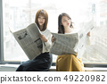 Two women reading a newspaper on the window side 49220982