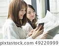 Two women reading a newspaper on the window side 49220999