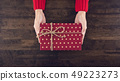 Woman hands giving a christsmas gift box top view 49223273