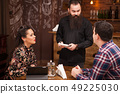 Waiter taking order from stylish couple in restaurant. 49225030
