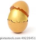 broken eggshell with golden egg inside 49226451
