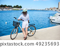 Young woman with backpack riding city bicycle near sea 49235693