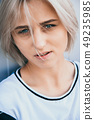 Portrait of cute girl with white short hairstyle. Her hair cover half face. She is looking forward 49235985