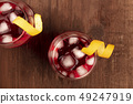 Two vibrant cocktails with campari, an orange curl garnish, and ice cubes, shot from the top on a 49247919