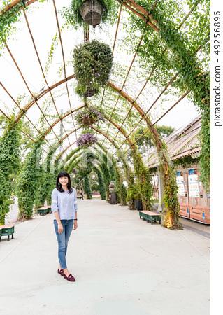 주한 공원으로 亞洲 여인. 공원으로 가게 꼭대기 及圍 란 佈滿 綠色 식물. 49256896