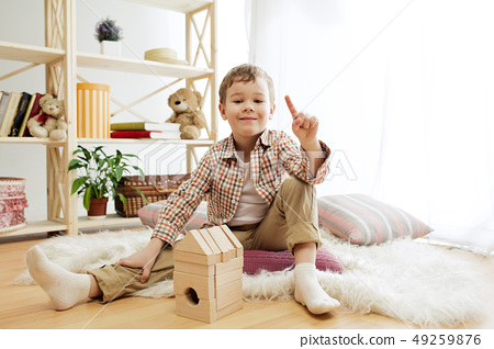 Little child sitting on the floor. Pretty boy palying with wooden cubes at home 49259876