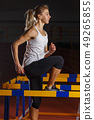 Young athletic sportswoman training with the hurdle 49265855