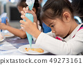 Cute asian child girl decorating cookies with fun 49273161