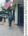 woman walking on street with fire hydrant in back 49274151