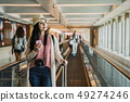 woman with luggage on moving walkway. 49274246
