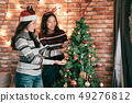 young asian girls decorating Christmas tree 49276812