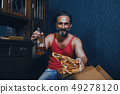 Handsome hungry man is eating pizza. 49278120