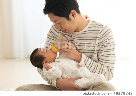 Father childcare nursery men who causes the baby to drink milk in a feeding bottle 49279848