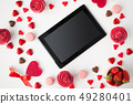 close up of tablet pc and sweets on valentines day 49280401