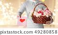 man holding basket of flowers with greeting card 49280858