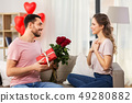 happy man giving woman flowers and present at home 49280882