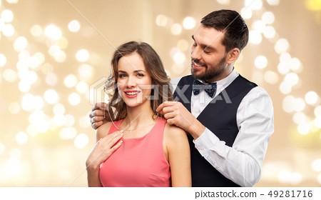 happy man puts necklace on his girlfriend 49281716