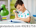 boy with magnifier reading book at home 49281756