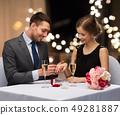 man giving woman engagement ring at restaurant 49281887