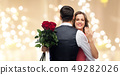 woman with engagement ring and roses hugging man 49282026